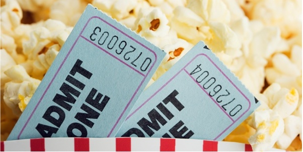 A pair of movie tickets with popcorn behind them.